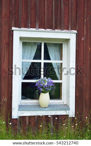 A jug full of meadow flowers on a window sill of an old house
