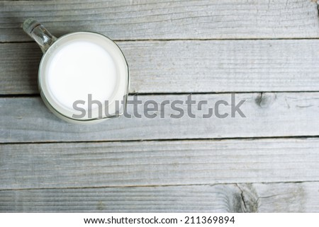 a jug of milk on old wooden table - stock photo