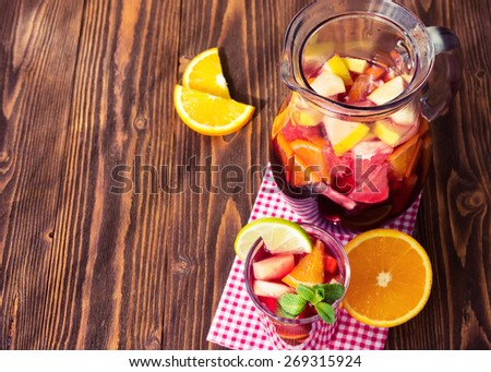 A jug of refreshing sangria with fruits on wooden background - stock photo
