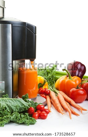 A Juicer surrounded by healthy fruits and vegetables on white with shadows.
