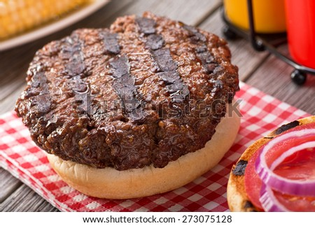 A juicy barbecued hamburger with grill marks on a rustic picnic table with tomato, onion, mustard, ketchup, and corn. - stock photo