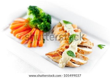 A juicy chicken breast grilled and topped with alfredo sauce and steamed carrots and broccoli as side dish. Shallow depth of field on first slices of chicken