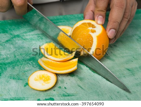 A juicy orange being sliced into segments. - stock photo