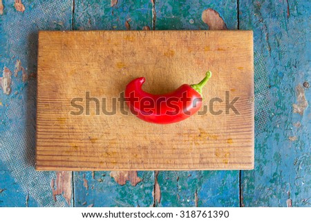 a juicy red peppers on a cutting board on a bright wooden table - stock photo