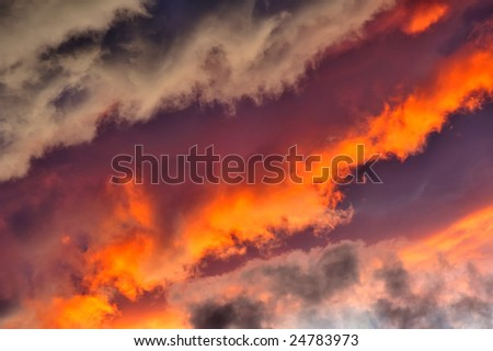A jumble of stratocumulus clouds at sunset arranged in lines with a diagonal composition. Suitable as an abstract, natural graphics background. - stock photo