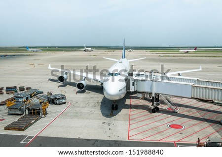 A jumbo jet is parked at the boarding gate.