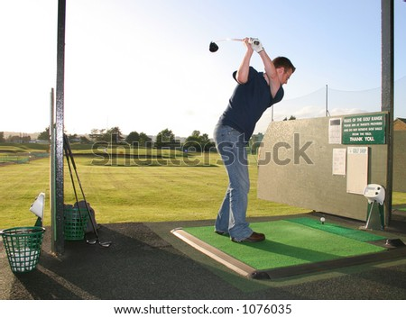 A junior golf champion practices on the golf range