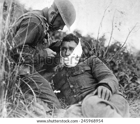 A just wounded American soldier, receiving first-aid treatment from a comrade. WWI. Varennes-en-Argonne, France. Sept. 26, 1918 - stock photo
