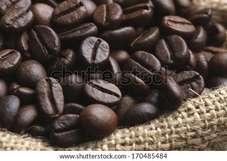 A juta bag with roasted coffee beans - stock photo