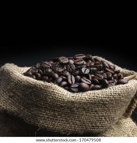 A juta bag with 	roasted coffee beans, on black background - stock photo