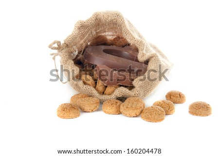 "A jute bag full of pepernoten and a chocolate letter, for celebrating a dutch holiday "" Sinterklaas ""  on the fifth of December - stock photo"