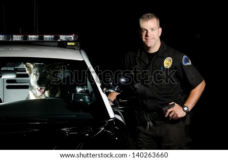 A K9 handler standing next to his patrol car with his partner in the driver seat. - stock photo