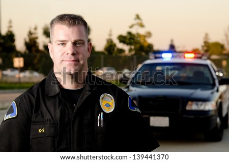 A K9 police officer standing in front of his patrol car at dusk. - stock photo