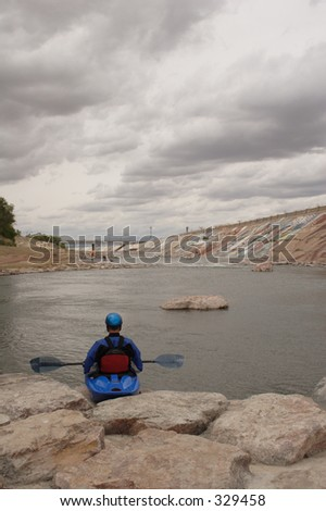A kayaker gets ready to take the plunge into the man-made kayak run near downtown Pueblo, Co., on the Arkansas River.  Taken in May, 2005. - stock photo
