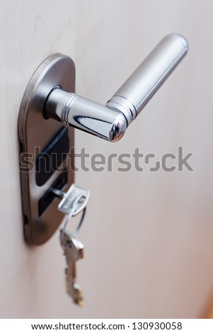 A key in a lock at safety door. - stock photo