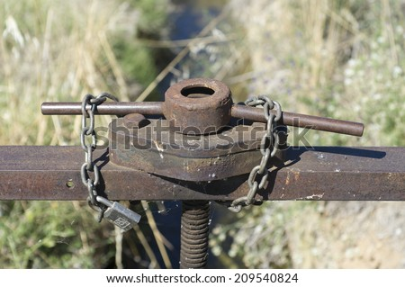 a key step padlocked water in an irrigation canal - stock photo