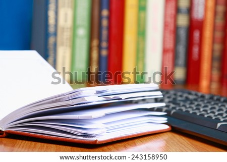 A keyboard and open notebook against books on the desk - stock photo