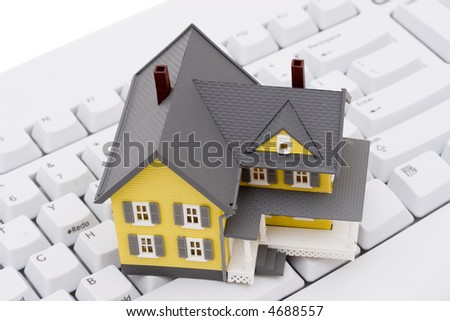 A keyboard with bright yellow house - stock photo