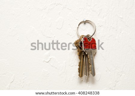 A keyring with three keys  hanging on nail on wall.