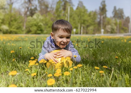 A kid laying down with his soccer ball in the middle of a field