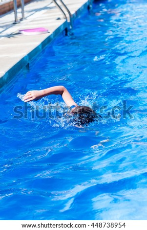 A kid swimming croll style during his swimming practice.