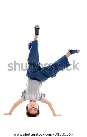 A kid upside down smiling to the camera, looking like a circus artist or maybe a capoeira fighter which is a native Brazilian fight style. Isolated on white. - stock photo