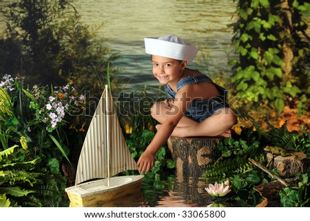 A kindergarten boy in a sailor's hat sailing a toy boat by the waters' edge. - stock photo