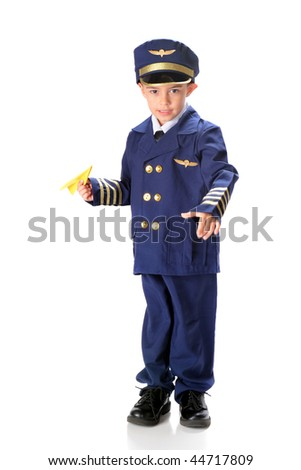 A kindergarten boy in an over sized airline pilot uniform ready to launch a paper airplane.