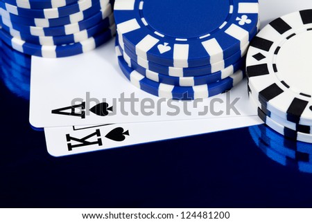 A king and ace of spades under a pile of poker chips on a shiny blue background. - stock photo