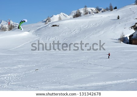 A kite boarder being pulled across the snow by his kite.