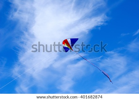 a kite hovers in the air against a blue sky with clouds