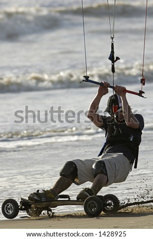 A kite skateboarder rides the sand with his