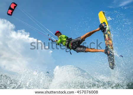 A kite surfer rides the waves - stock photo