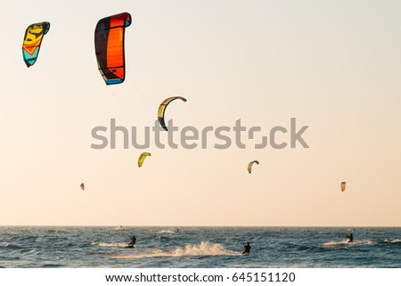 A kite surfers rides the waves in golden sunlight