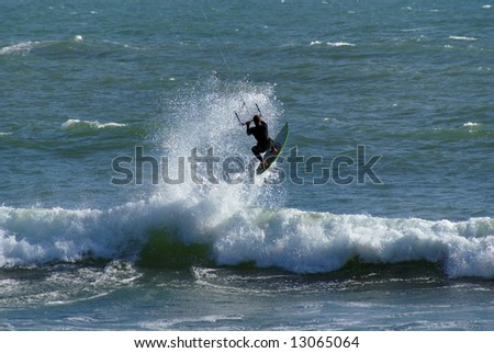 A kitesurfer is pulled up high in the air by his kite. - stock photo