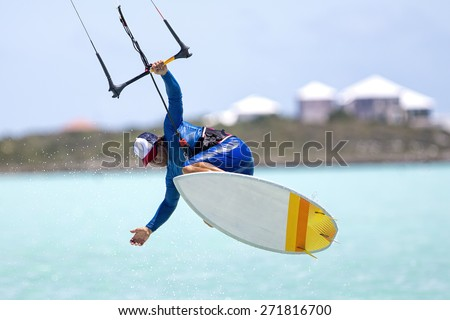 A kitesurfer performing an aerial trick riding strapless surfboard on a sunny day. - stock photo