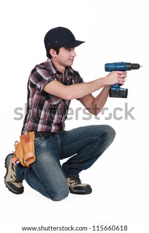 A kneeled handyman drilling. - stock photo