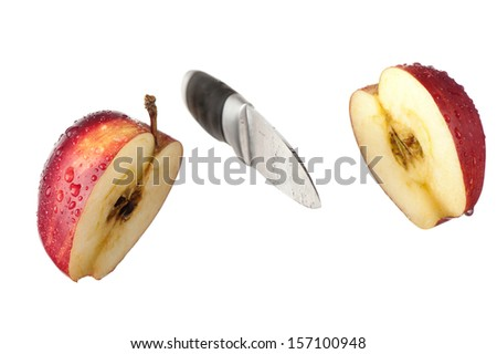 A knife and an apple cut in half are frozen in mid air. - stock photo