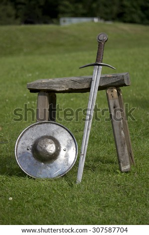 A knight's sword and shield resting against a stool - stock photo