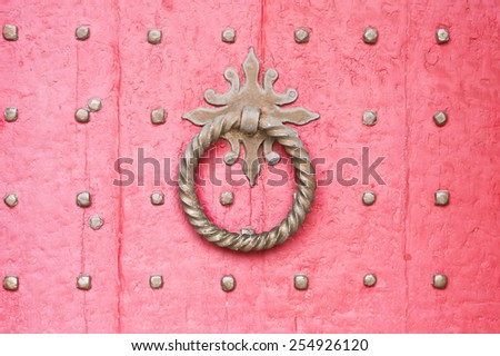 A knocker on a red medieval door - stock photo