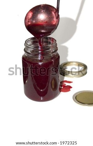 a ladle pouring jelly into a jar