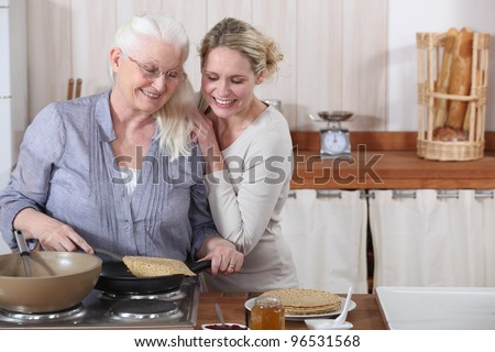 A lady and her daughter cooking crepes. - stock photo