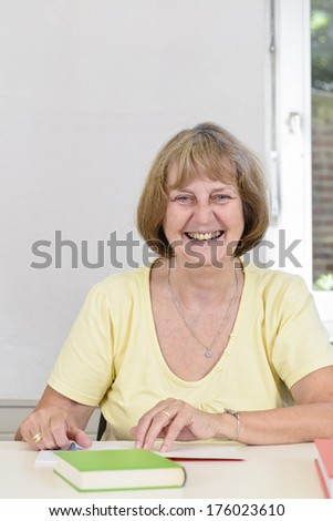 A lady is sitting at the table smiling.