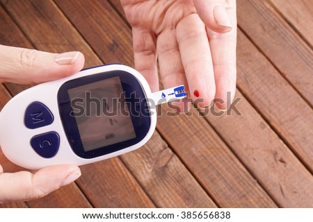 a lady's hands measuring blood sugar, glucose with a home test to control her diabetes - stock photo