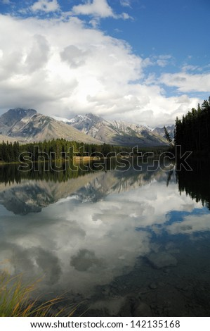 A lake in Banff Park, Canada reflects mountains and bright clouds in the late afternoon.