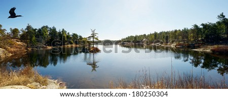 A lake in the early Spring with a tiny islet with three weathered trees in Northern Ontario, Canada. Wide angle.  - stock photo