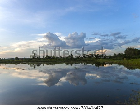 A lake in the Thai countryside mirrors the clouds at sunset
