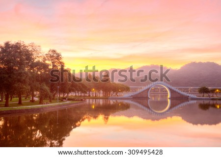 A lakeside park lit up by golden sunlight with refections of an arch bridge and glowing sky on the smooth lake water ~ Early morning scene of Dahu Community Park in Nahu,Taipei City Taiwan - stock photo