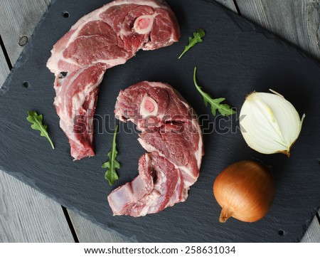 A lamb shoulder chops. Raw meat with onion on black stone. - stock photo