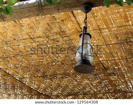 A lamp hanging from a ceiling made of wicker. - stock photo